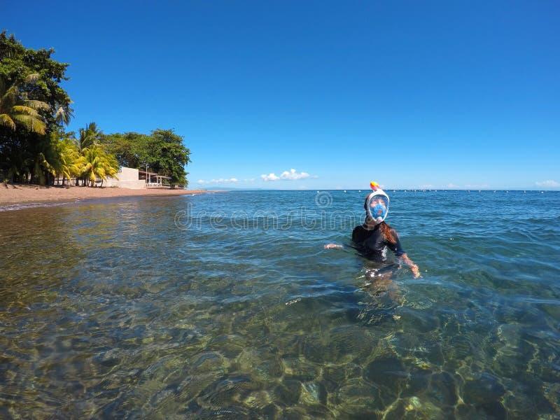 Härlig kvinna i den snorkla maskeringen i det blåa havet nära den tropiska stranden arkivbilder