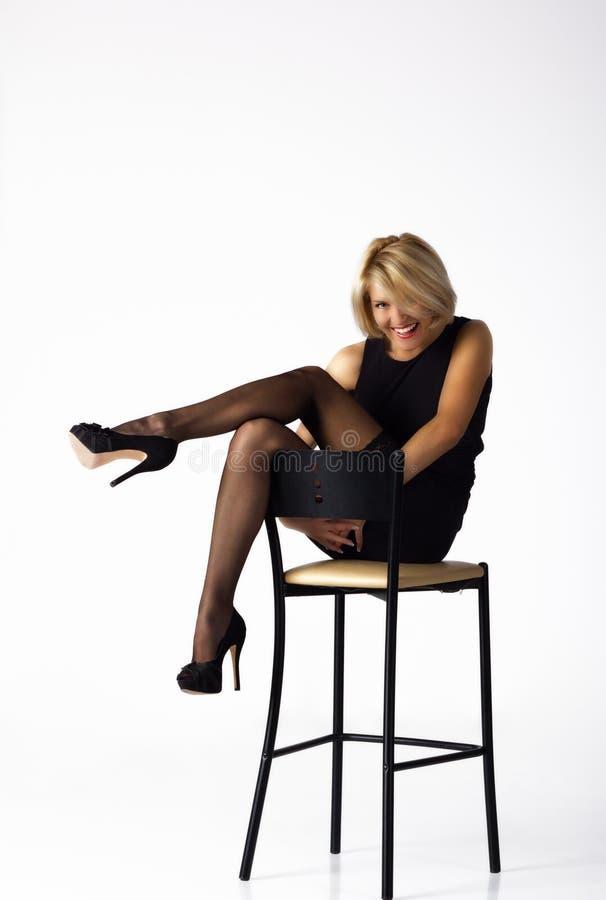Härlig kvinna i den svarta klänningen som poserar sammanträde på en stol royaltyfri fotografi