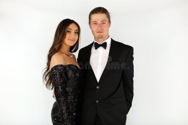 Härlig kvinna i den tillbaka studentbalklänningen och den stiliga grabben i dräkt, sexig tonåring som är klar för en lyxig natt royaltyfri bild