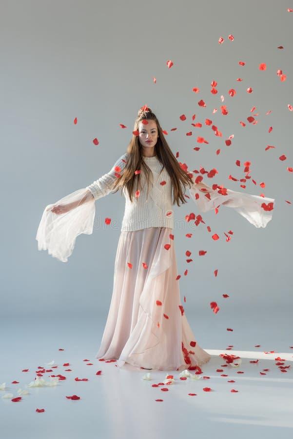 härlig kvinna i den trendiga vinterdräkten som omkring rotera under fallande kronblad för röda rosor royaltyfria foton