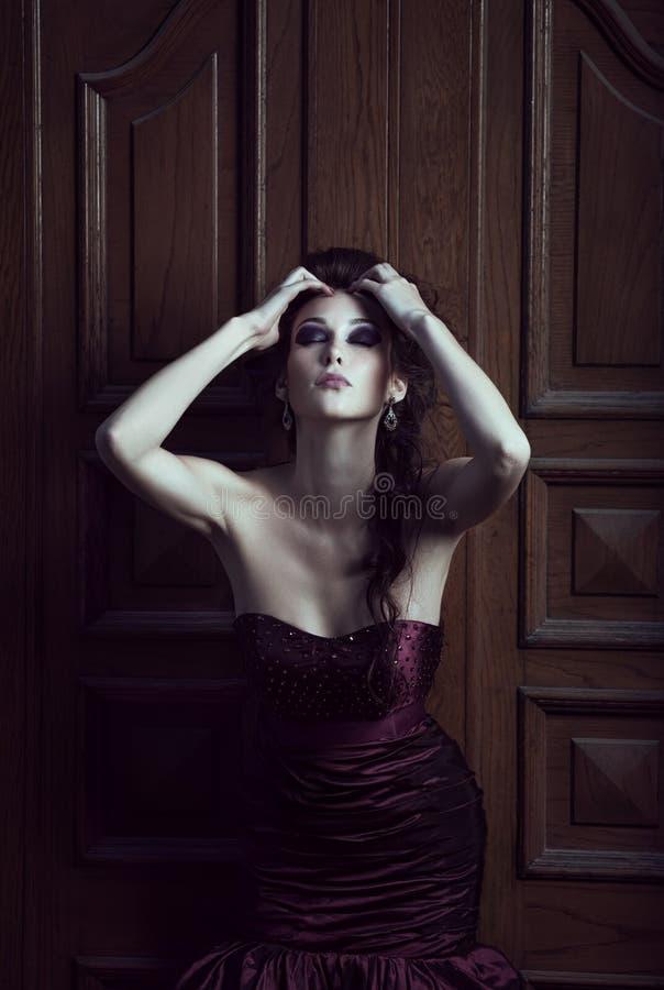 Härlig kvinna i den violetta klänningen royaltyfri foto