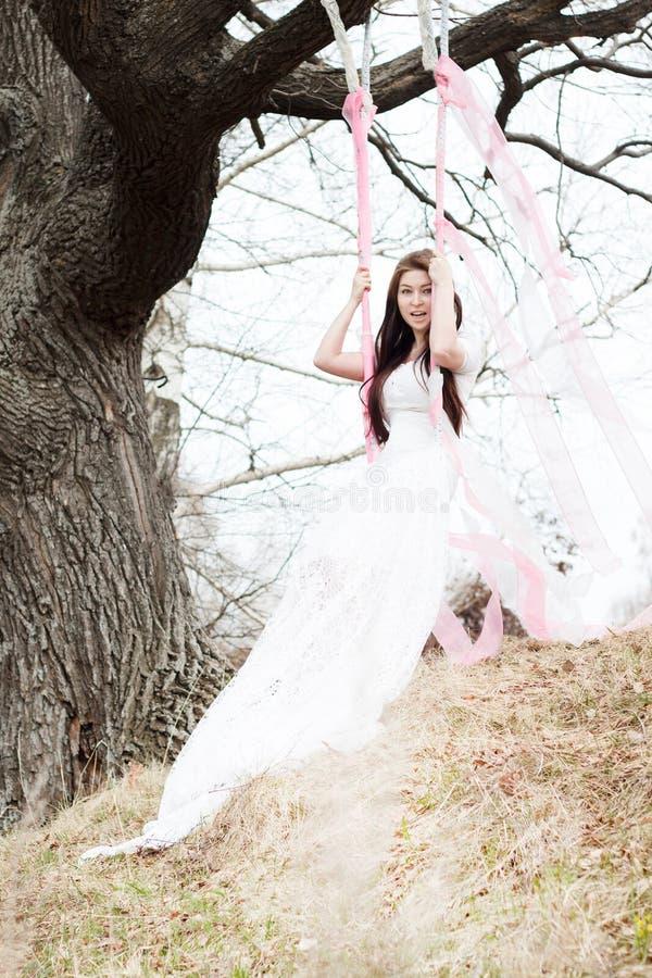 Härlig kvinna i den vita bröllopsklänningen som skakar på en gunga royaltyfri fotografi