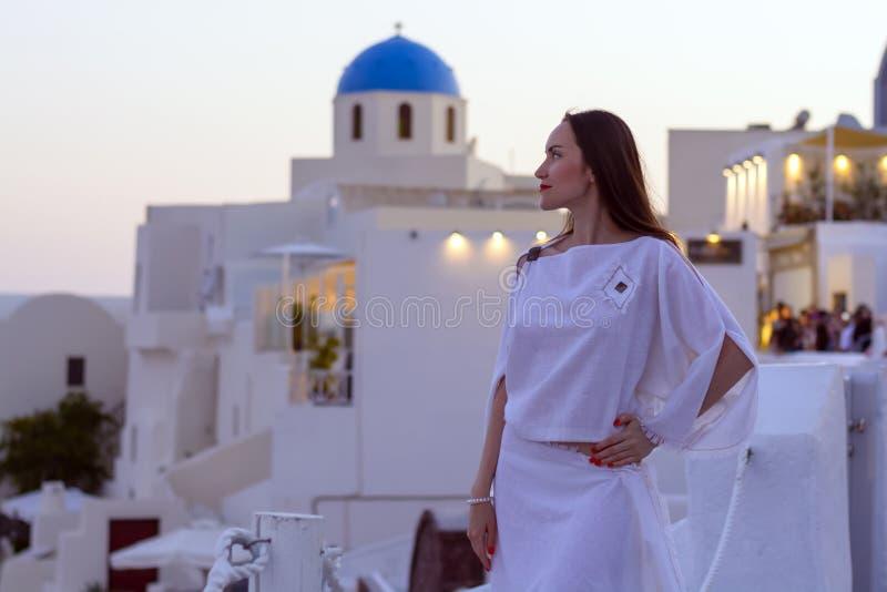 Härlig kvinna i den vita klänningen på bakgrund av arkitekturen i Santorini Solnedgång arkivbild