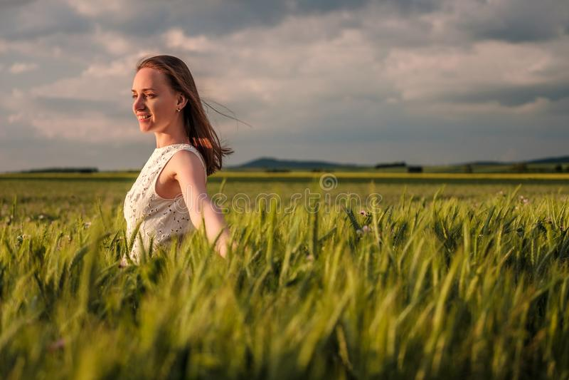 Härlig kvinna i den vita klänningen på grönt vetefält royaltyfri fotografi