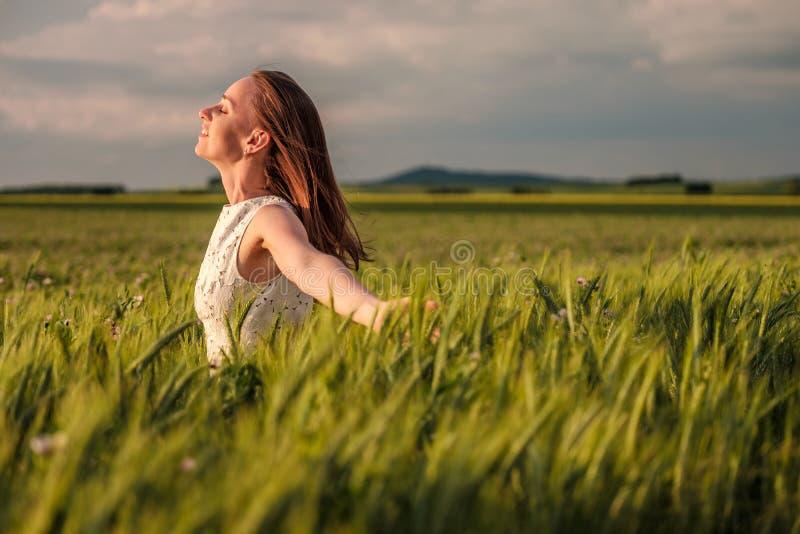 Härlig kvinna i den vita klänningen på grönt vetefält arkivfoto