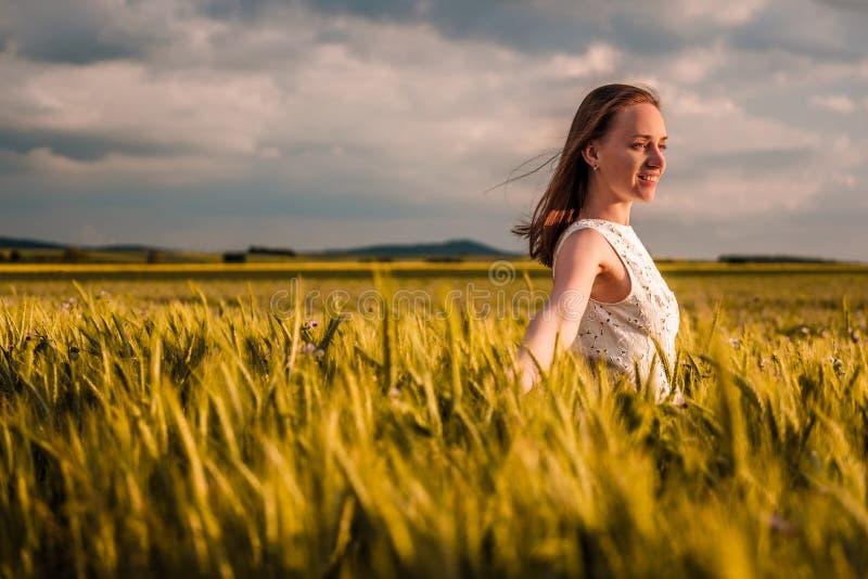 Härlig kvinna i den vita klänningen på guld- gult vetefält arkivbild