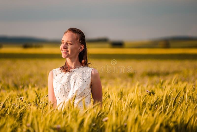 Härlig kvinna i den vita klänningen på guld- gult vetefält royaltyfri foto
