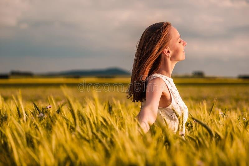 Härlig kvinna i den vita klänningen på guld- gult vetefält arkivfoto