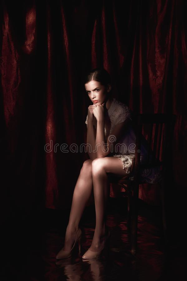 Härlig kvinna i den vita klänningen på mörk burgundy bakgrund royaltyfria bilder