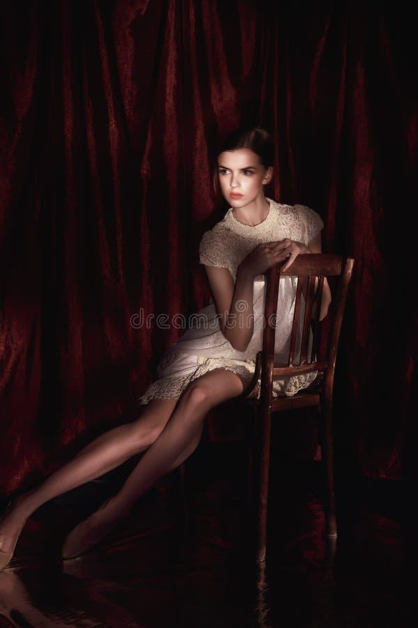 Härlig kvinna i den vita klänningen på mörk burgundy bakgrund arkivbilder