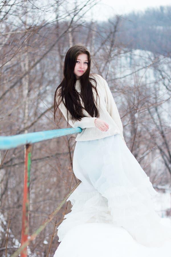 Härlig kvinna i den vita klänningen på vinterlandskap arkivbild