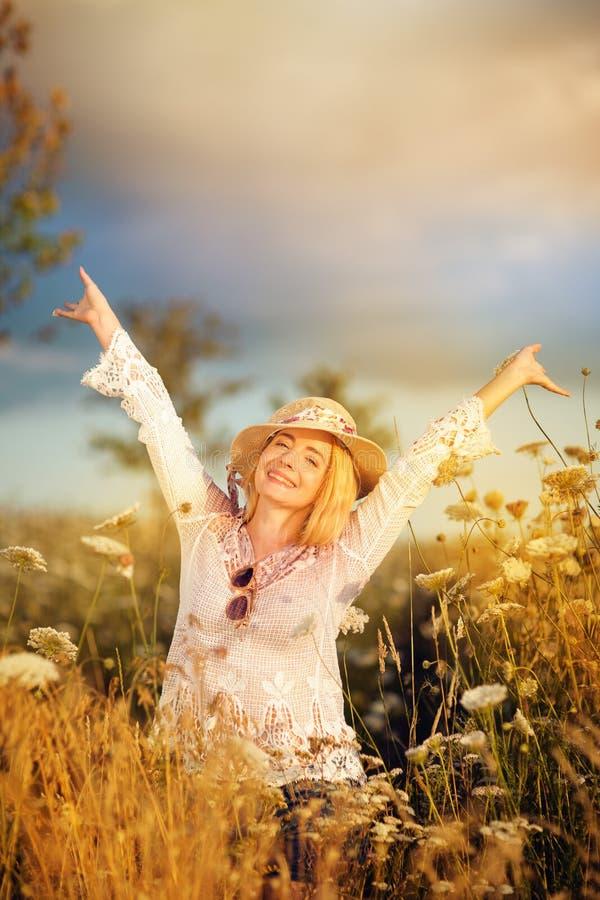 Härlig kvinna i en blommaäng med sunhat och solglasögon, lusta för liv royaltyfria bilder