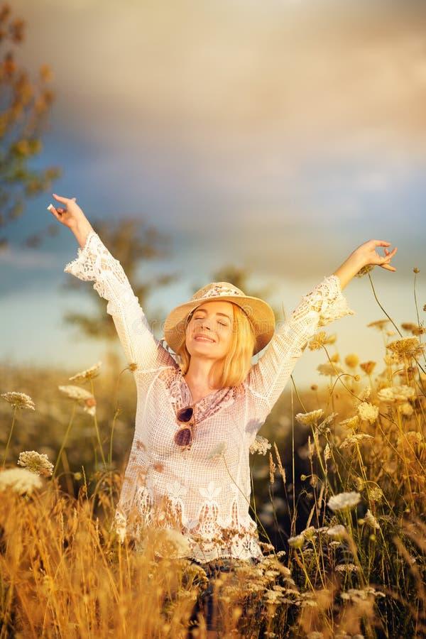 Härlig kvinna i en blommaäng med sunhat och solglasögon, lusta för liv royaltyfri bild