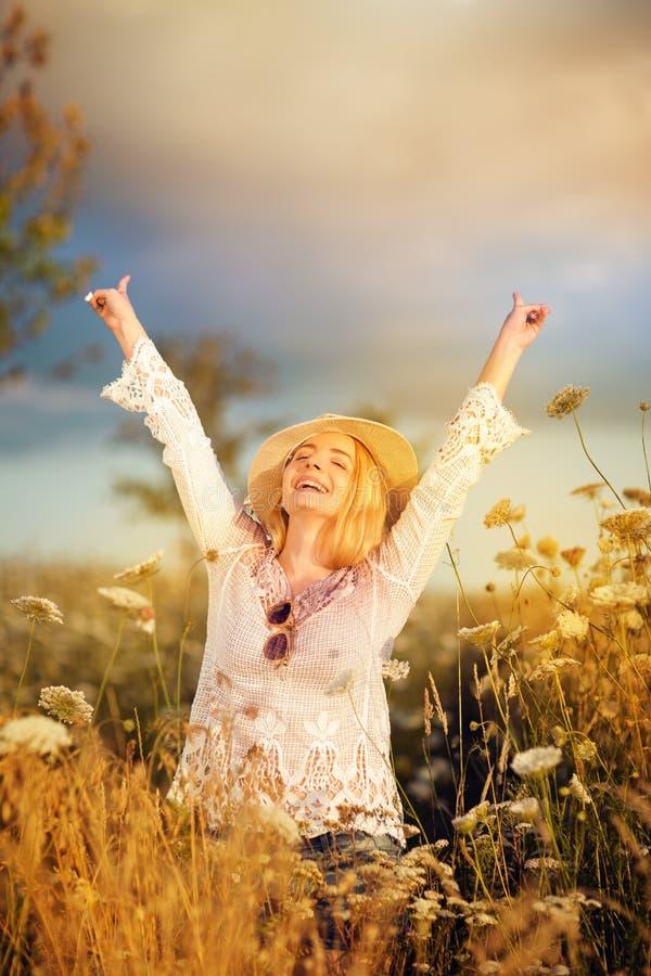 Härlig kvinna i en blommaäng med sunhat och solglasögon, lusta för liv royaltyfri fotografi