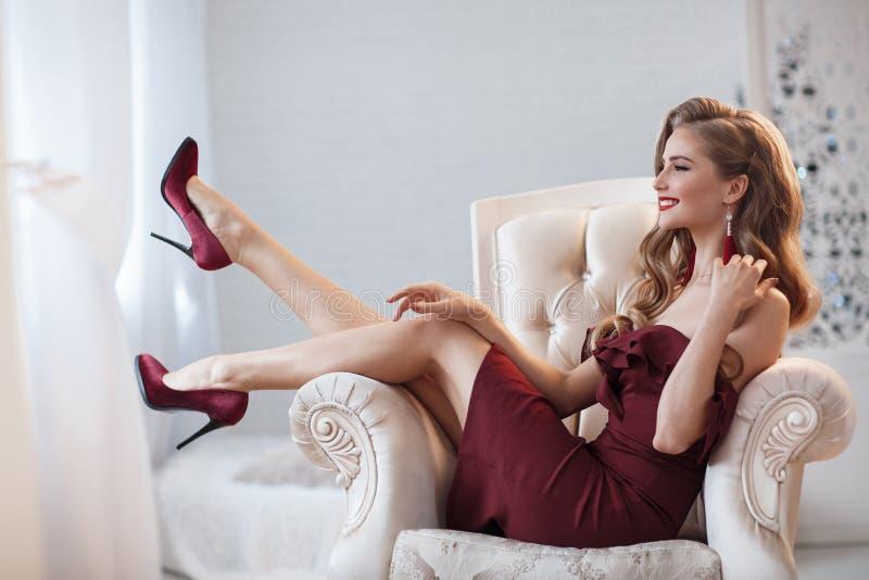 Härlig kvinna i en elegant utomhus- klänning som bara poserar och att sitta i en stol arkivbild