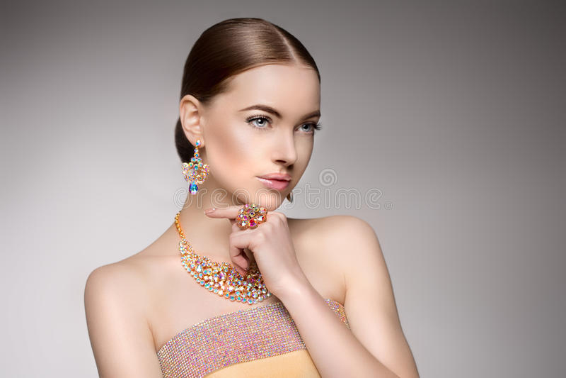 Härlig kvinna i en halsband, örhängen och cirkel Modell i juvel royaltyfri bild