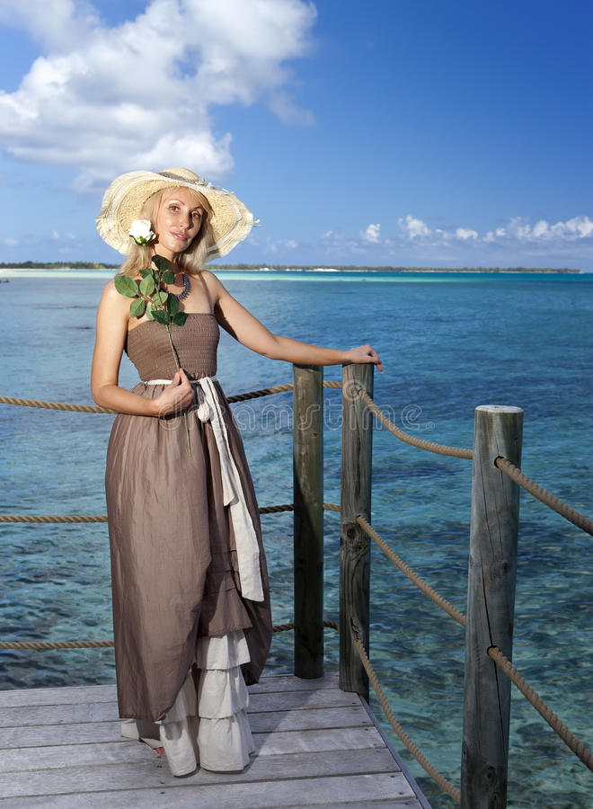 Härlig kvinna i en lång klänning på en träplattform över havet arkivfoton