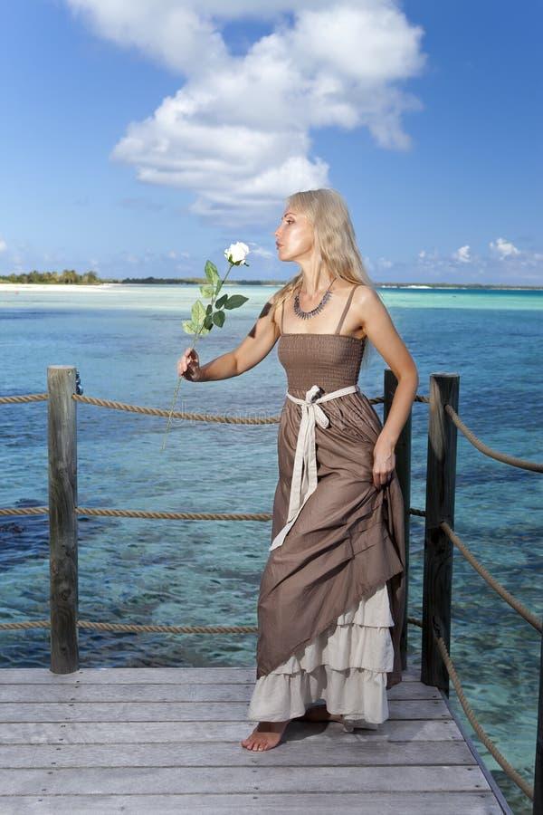 Härlig kvinna i en lång klänning på en träplattform över havet royaltyfria foton
