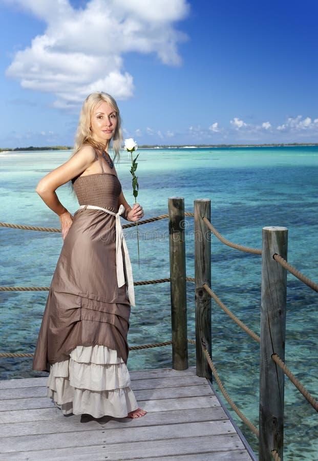 Härlig kvinna i en lång klänning på en träplattform över havet royaltyfri bild