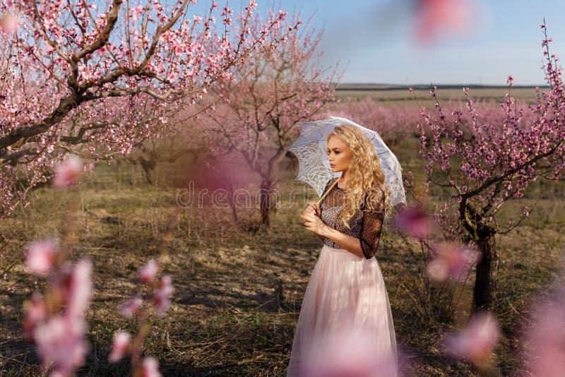 Härlig kvinna i en lång klänning, i trädgården av blommande persikor royaltyfri bild