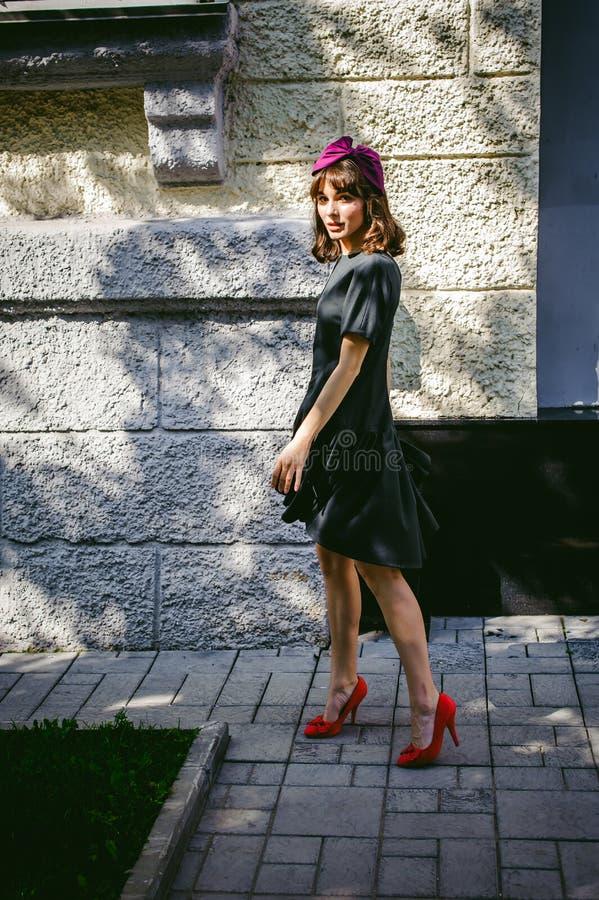Härlig kvinna i en mörk stilfull klänning Stående av en trendig gi arkivfoton