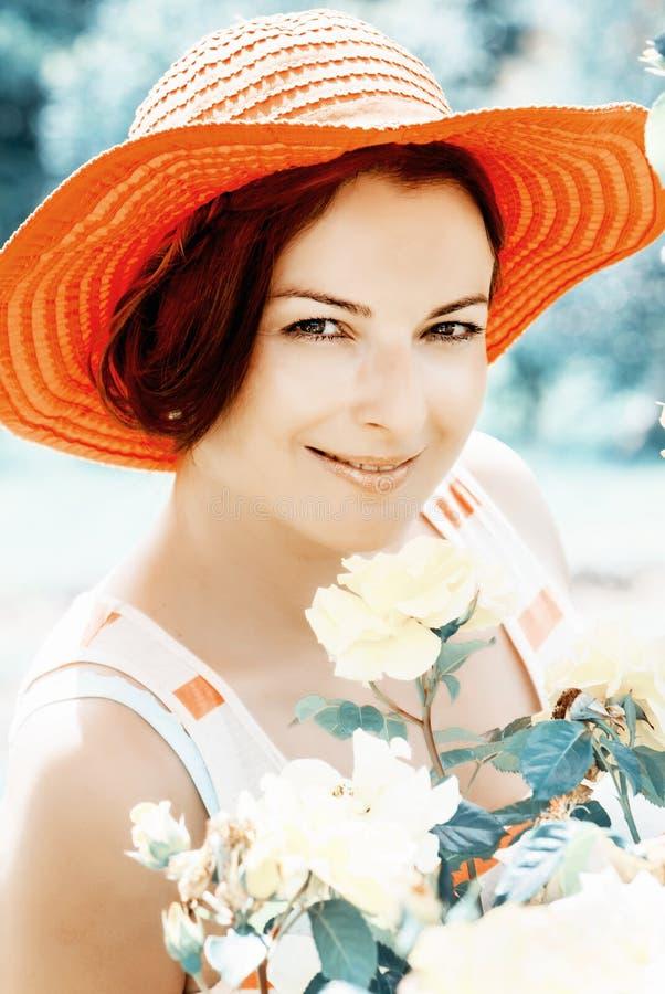 Härlig kvinna i en röd hatt som poserar i trädgård royaltyfri foto