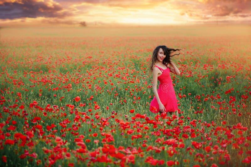 Härlig kvinna i en röd klänning i ett vallmofält på solnedgången som fladdrar hår, varm toning, lycka och en sund livsstil royaltyfri bild
