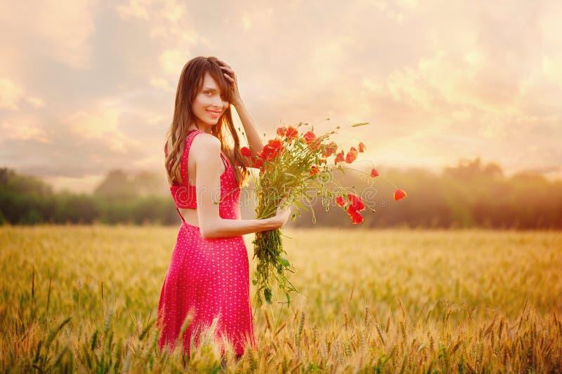Härlig kvinna i en röd klänning med en bukett av vallmo i ett vetefält på solnedgången, den varma toningen, lycka och en sund lif royaltyfria foton