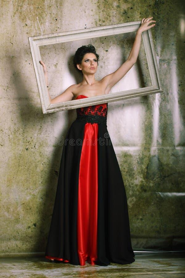Härlig kvinna i en röd och svart klänning fotografering för bildbyråer