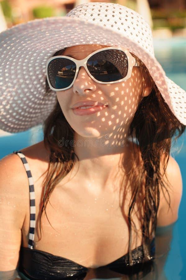 Härlig kvinna i en stor vit hatt och solglasögon på bakgrunden av pölen fotografering för bildbyråer