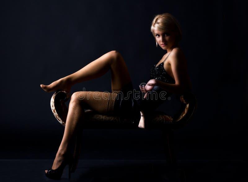 Härlig kvinna i en svart klänning på en mörk bakgrund royaltyfria foton