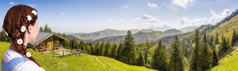 Härlig kvinna i en traditionell bavarian dirndl framme av ett berglandskap royaltyfri bild