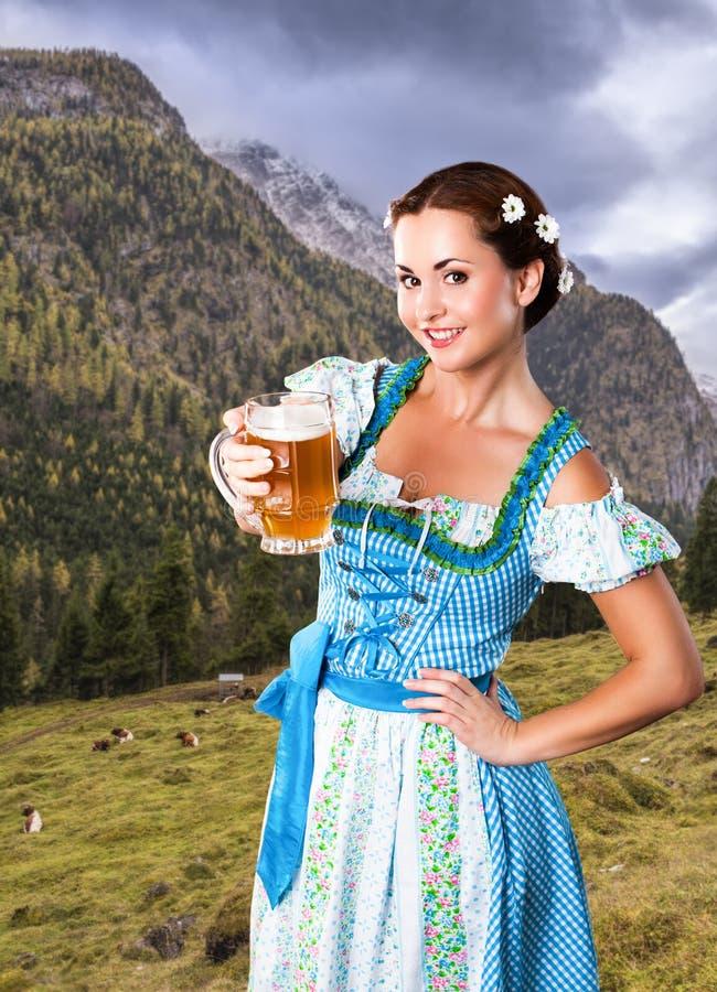 Härlig kvinna i en traditionell bavariandirndl med ett öl royaltyfria bilder