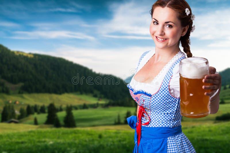 Härlig kvinna i en traditionell bavariandirndl med ett öl arkivfoton