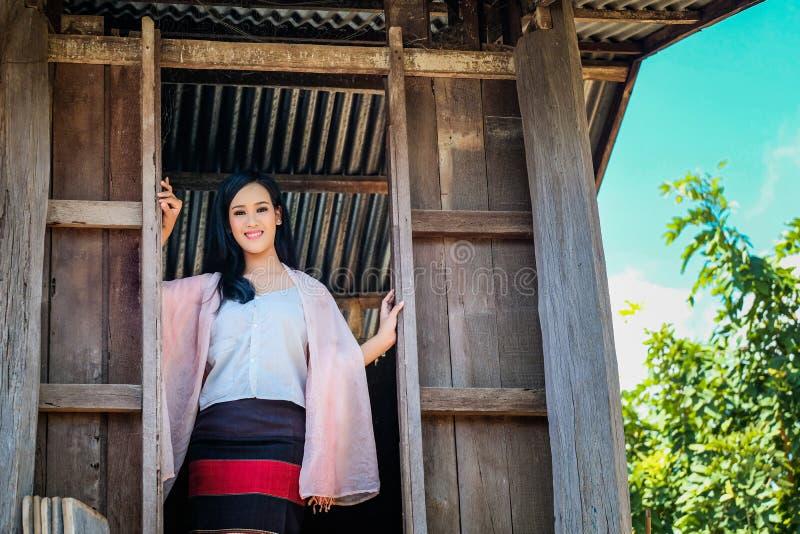 Härlig kvinna i en traditionell thailändsk klänningblått i en lantlig thailändsk atmosfär arkivfoton