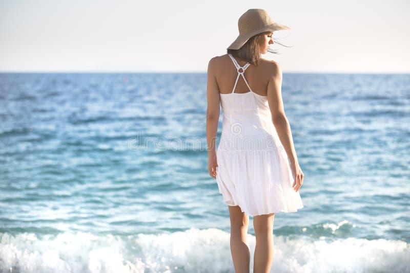 Härlig kvinna i en vit klänning som går på stranden Avkopplad kvinna som andas ny luft, emotionell sinnlig kvinna nära havet, enj royaltyfria bilder