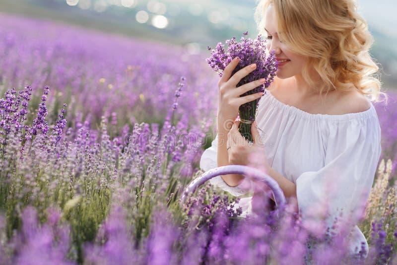 Härlig kvinna i ett fält av att blomstra lavendel royaltyfri fotografi