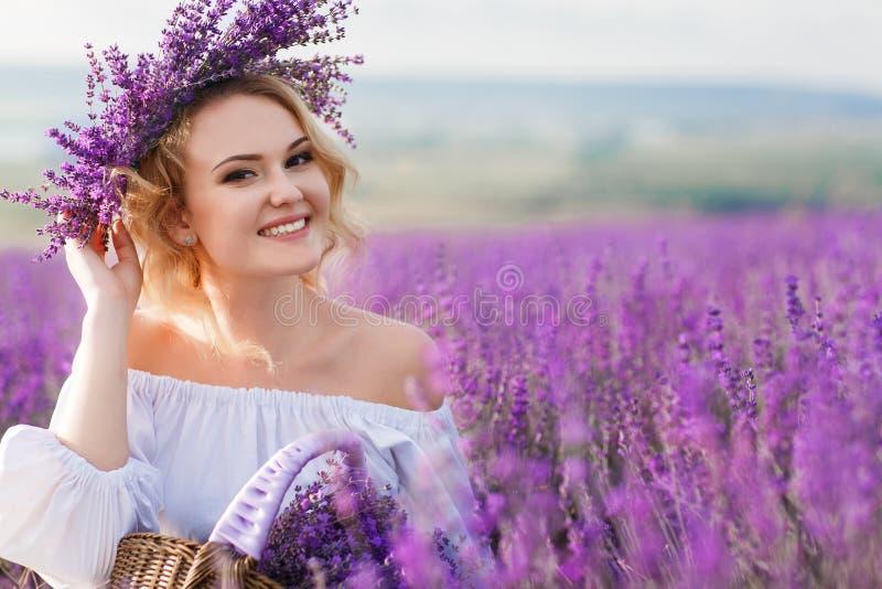 Härlig kvinna i ett fält av att blomstra lavendel arkivfoto