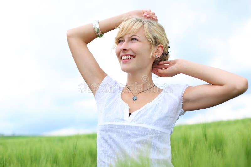 Härlig kvinna i ett grönt fält arkivfoto