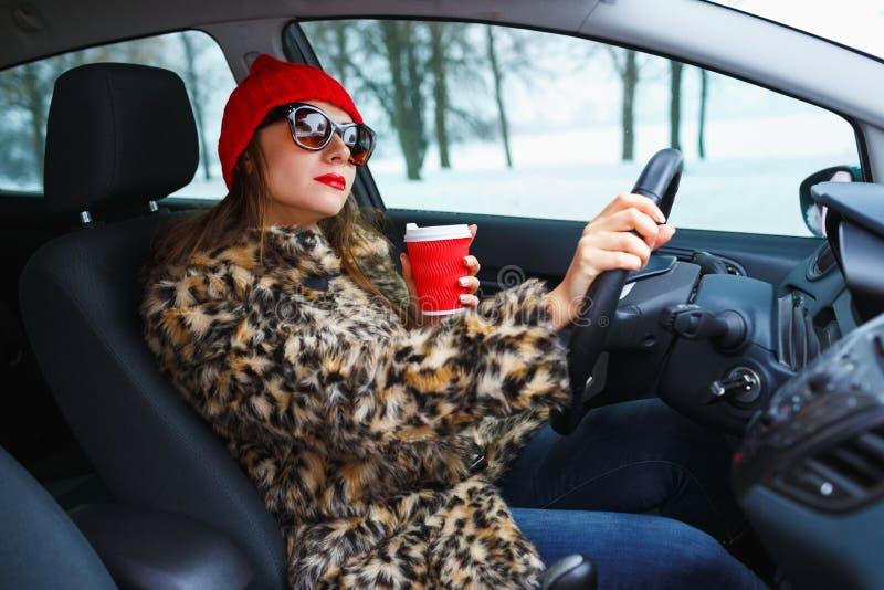 Härlig kvinna i ett pälslag och en röd hatt med kaffe som går driv royaltyfri fotografi