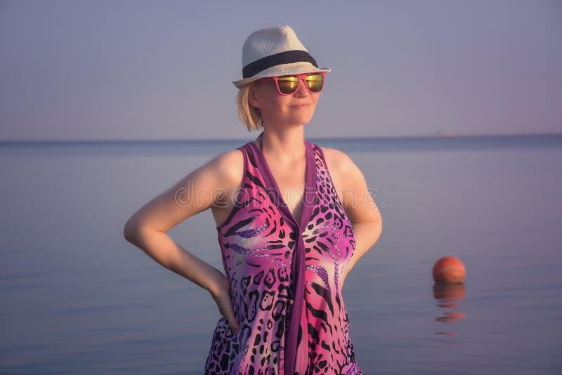 Härlig kvinna i ett purpurfärgat klänninganseende i vattnet med trevlig solnedgång arkivfoton