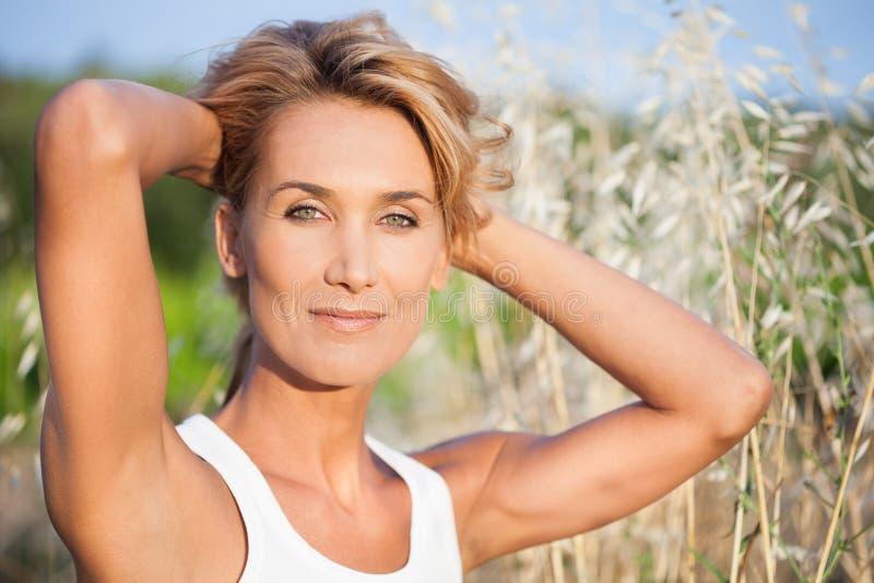 Härlig kvinna i fälten i sommar arkivfoto