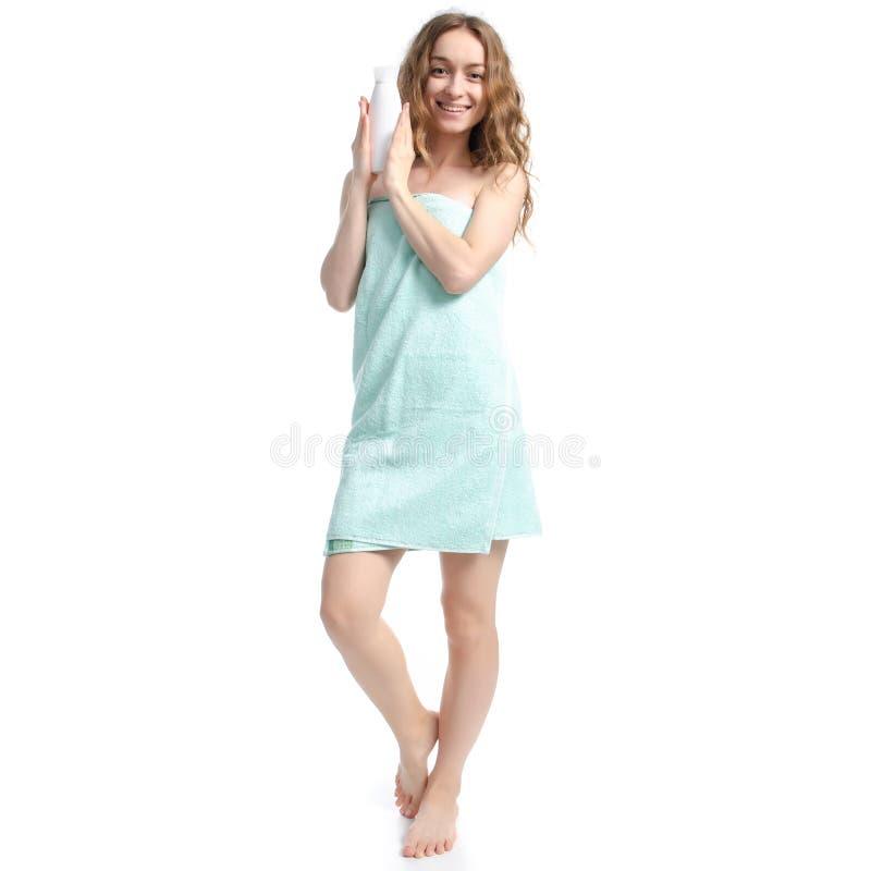 Härlig kvinna i för flaskkräm för grön handduk vit lotion i omsorg för handskönhetkropp royaltyfria foton