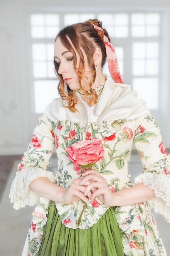 Härlig kvinna i grön medeltida klänning med blomman royaltyfri foto