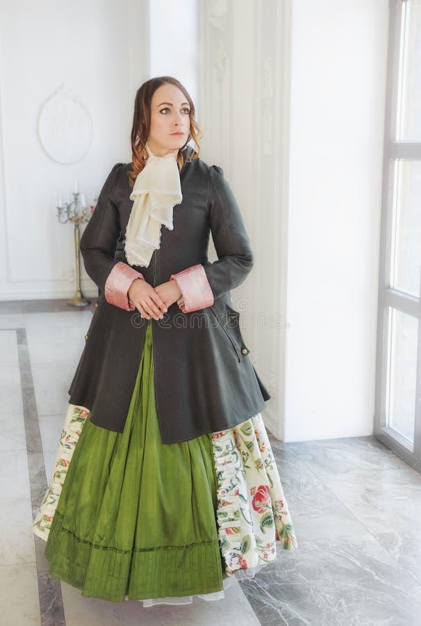 Härlig kvinna i grön medeltida klänning och bonjour nära vind fotografering för bildbyråer