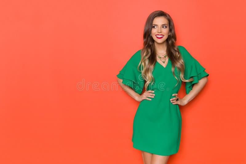 Härlig kvinna, i gröna Mini Dress Is Looking Away och att le royaltyfria foton