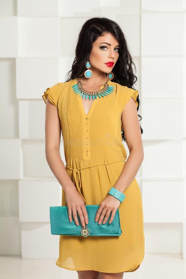 Härlig kvinna i gul klänning och moderiktig blå tillbehör fotografering för bildbyråer