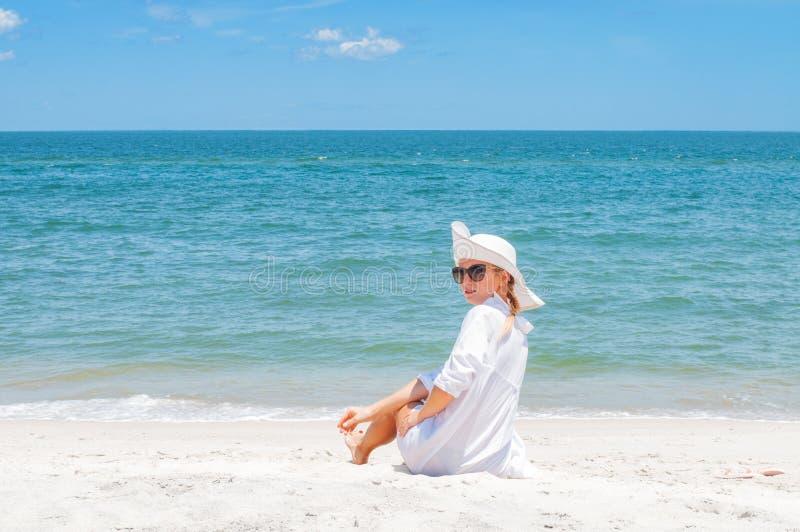 Härlig kvinna i hattsammanträde på stranden som tycker om sommarferier arkivfoton