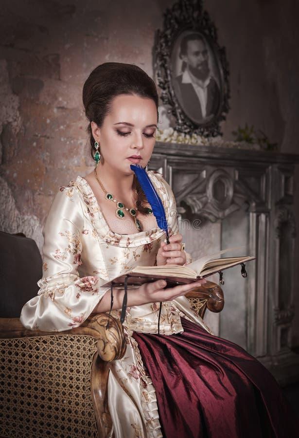 Härlig kvinna i historisk medeltida klänning med dagboken arkivfoto