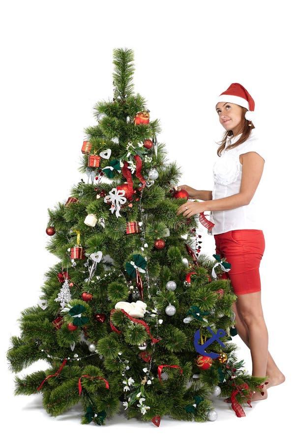 Härlig kvinna i jultomtenlock som dekorerar julgranen royaltyfria foton